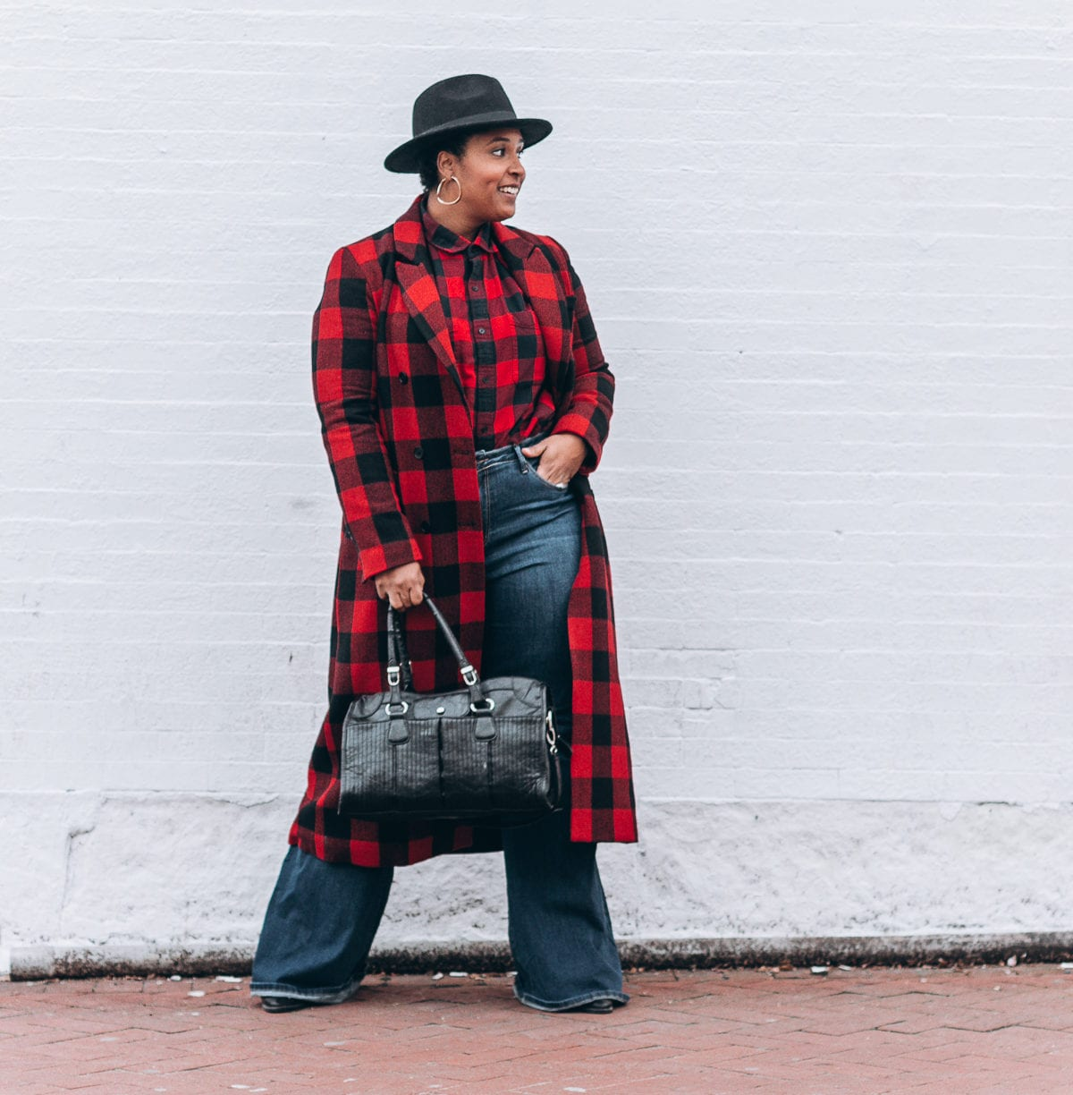 top baltimore blogger wearing bold prints buffalo check walking in the streets of dc bell bottom jeans how to style
