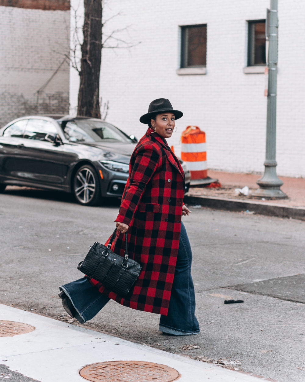 top washington dc blogger jen jean pierre wearing a double buffalo print red  and black shirt with matching long overcoat black fedora hat and bell bottom  ... 7bd982498104