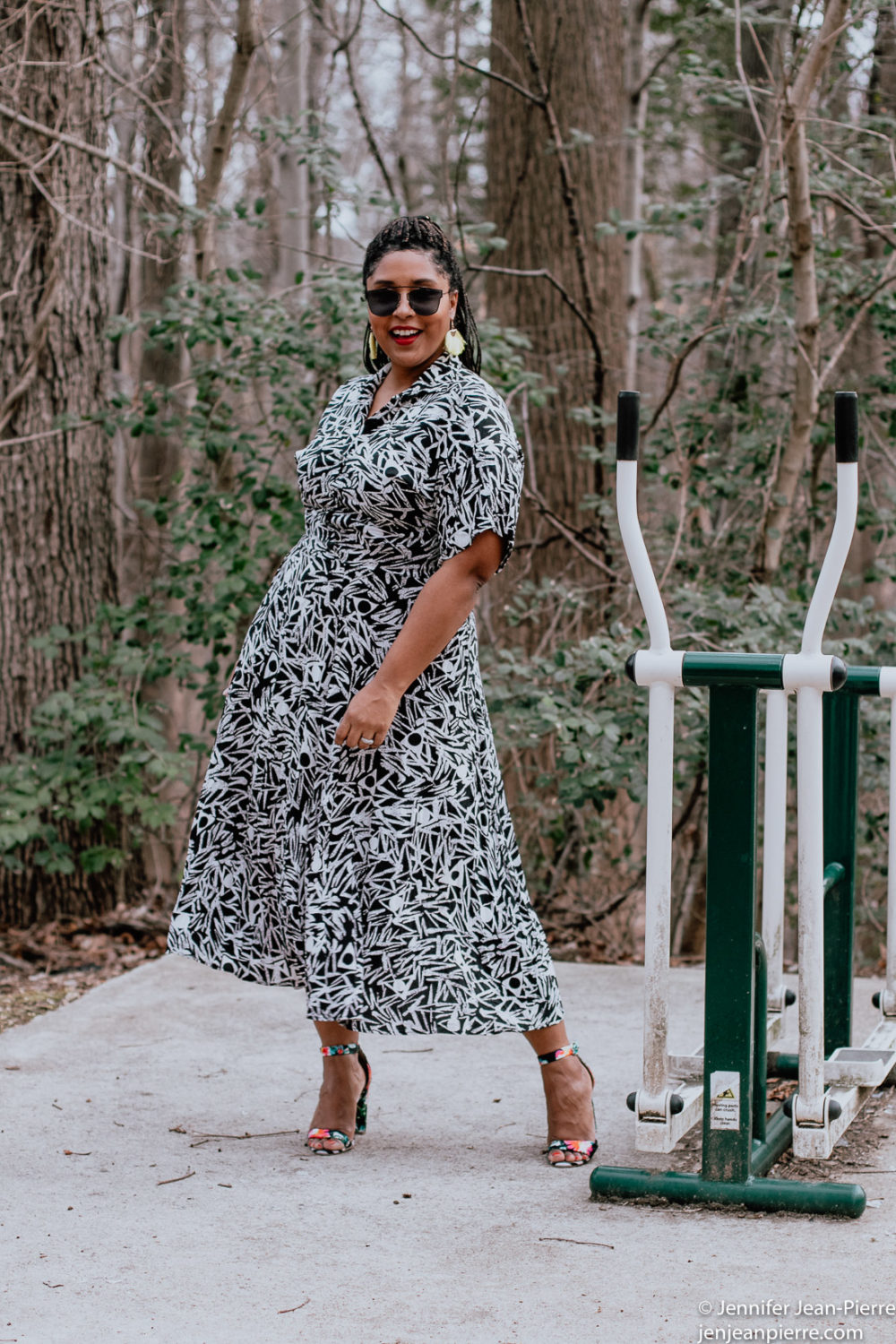 black girl wearing a long black and white print dress from thrift stores with yellow fringe earrings and hair back in a ponytail with black square glasses and floral black open toe sandals-8