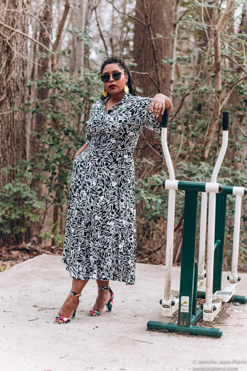black girl wearing a long black and white print dress with yellow fringe earrings and hair back in a ponytail with black square glasses and floral black open toe sandals-8