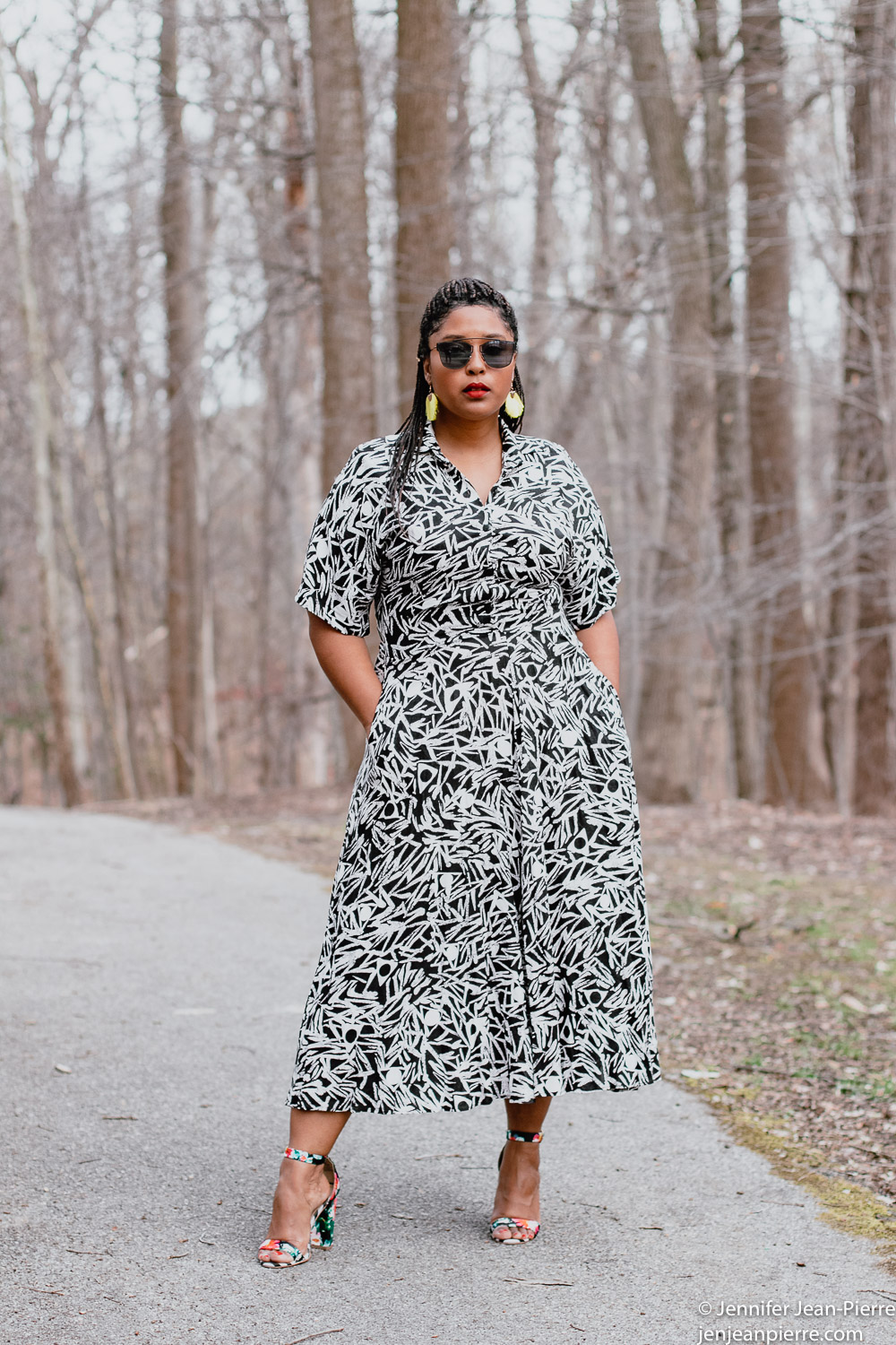 black girl wearing a long black and white print dress from the thrift stores with yellow fringe earrings and hair back in a ponytail with black square glasses and floral black open toe sandals