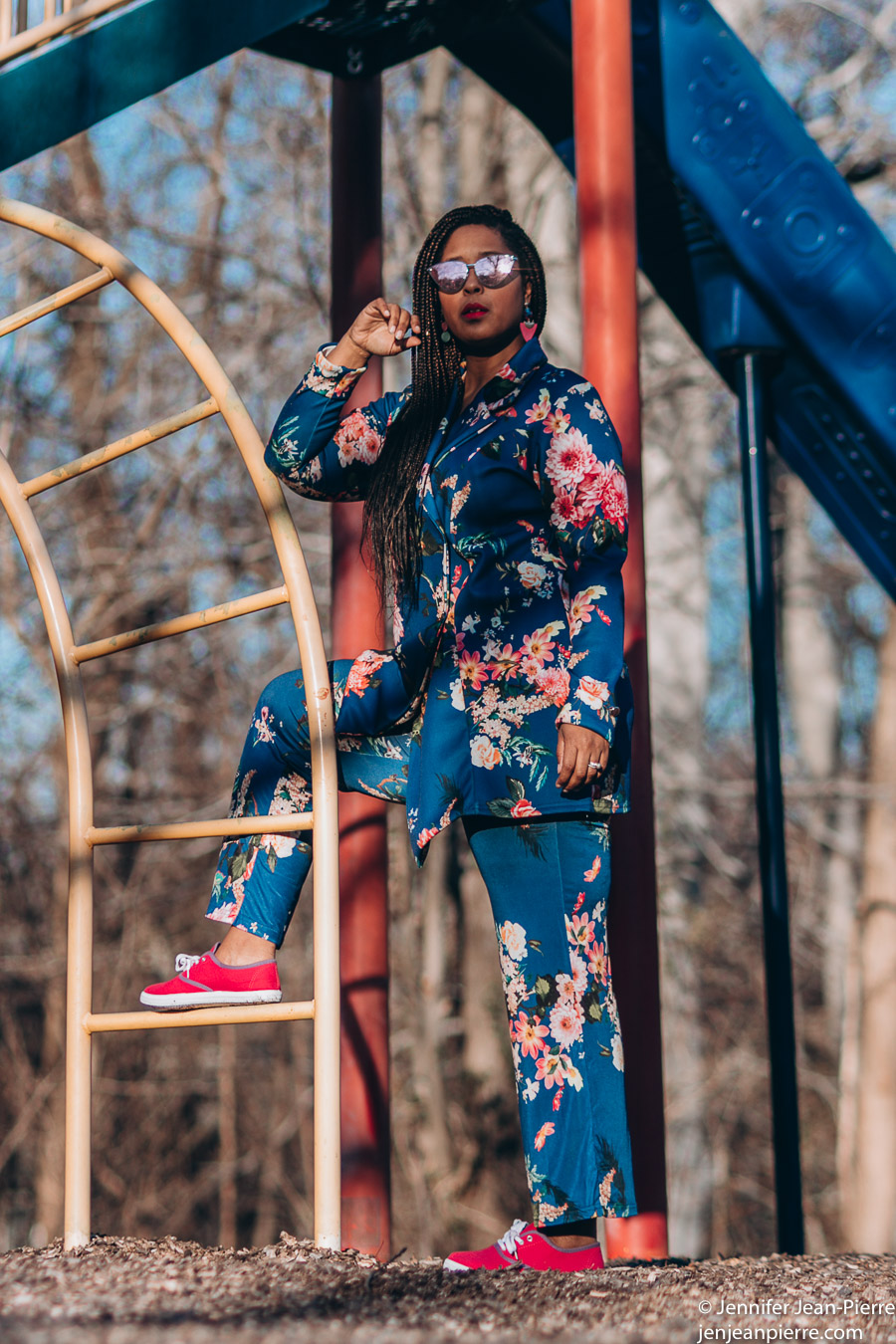 black girl wearing a blue floral suit with long braids at a playground